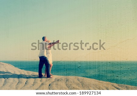 Young couple watching the sea holding hands. Filtered image: vintage, grunge and texture effects - stock photo