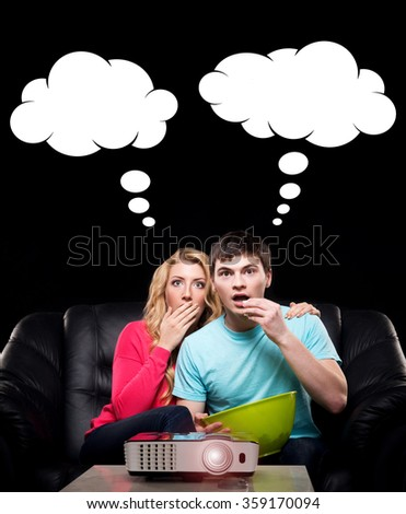 Young couple watching thrilling film on a laser projector. Comics concept.