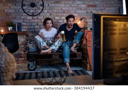 Young couple watching tv at home, jittering.
