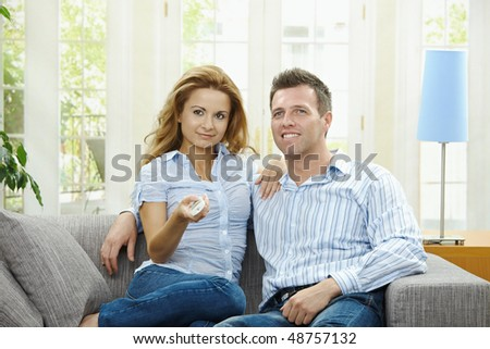 Young couple watching TV at home, sitting on couch, holding remote control in hand. - stock photo