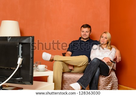 Young couple watching tv cuddling sitting armchair living room