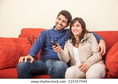 Young Couple Watching TV on the Sofa - stock photo