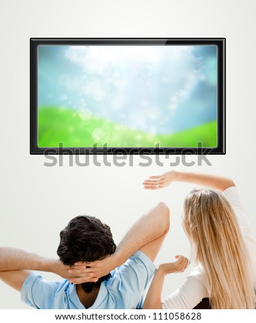 Young couple watching tv. Photo from behind. Lots of copyspace - stock photo