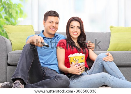 Young couple watching TV seated on the floor at home - stock photo