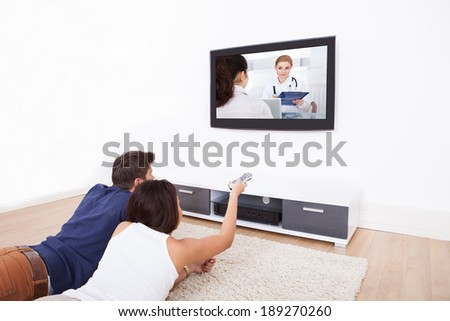 Young couple watching TV while lying on rug at home - stock photo