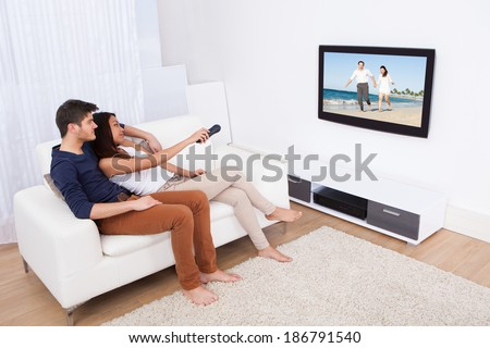 Young couple watching TV while sitting on sofa in living room at home - stock photo