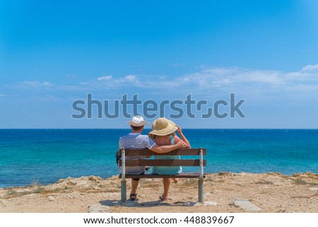 Young couple wearing braided hats sitting on a bench at a sea enjoying the view