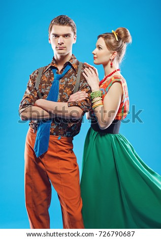 Young couple wearing colorful old-fashion clothes in pinup style