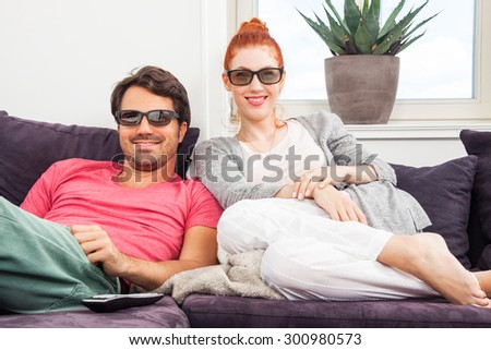 Young Couple Wearing 3D Glasses, Sitting on the Couch in the Living Room, Watching a Movie and Showing Shocked Faces.