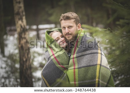 Young couple winter forest walk in a warm blanket  - stock photo