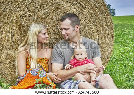 Young couple with a child sitting at the silage - stock photo