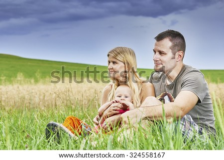 Young couple with a child sitting in the grass with sky in the background