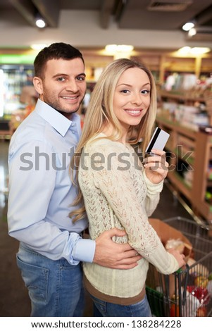 Young couple with a credit card in a store - stock photo