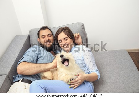 Young couple with a dog at home. Young man and a woman in blue shirts playing at home with them white scotch terrier.