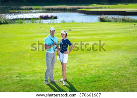 Young couple with a golf club on lawn