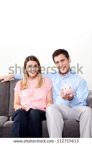 Young couple with a piggy bank sitting on couch