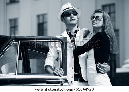 Young couple with a retro car. - stock photo