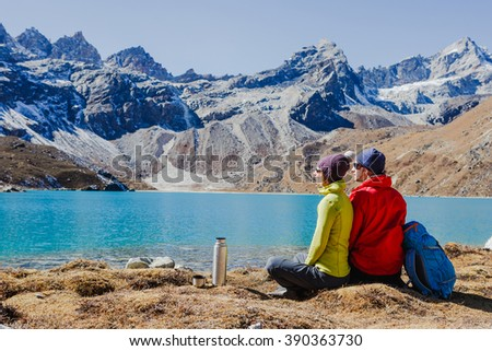 Young couple with backpacks relaxing near the lake in Himalayas. mountaineering, healthy lifestyle, fun concept - stock photo