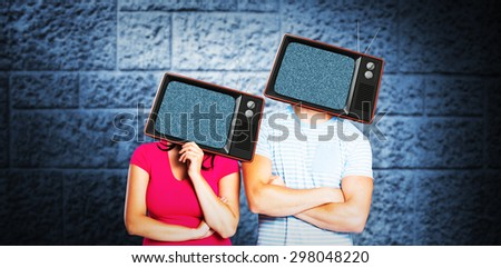 Young couple with bags over heads against dark grey room - stock photo
