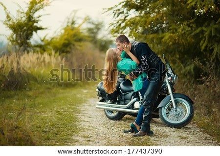 Young couple with beautiful bike on road.