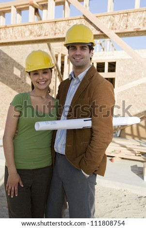 Young couple with blueprint at construction site - stock photo