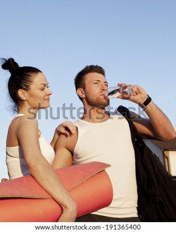 young couple with bottles of water against blue sky - stock photo