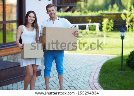 Young couple with boxes by the house - stock photo
