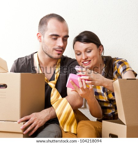 Young Couple with boxes in the new apartment sitting on floor and planning their future, dreaming about something positive