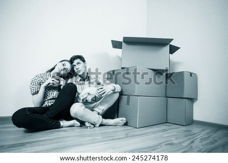 Young Couple with boxes of drinking coffee in the new apartment