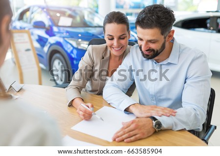Young couple with car dealer in auto salon