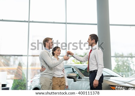 Young couple with car keys indoors - stock photo