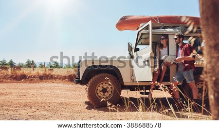 Young couple with car on road trip reading map for directions. Young man and woman taking break from the road trip. - stock photo