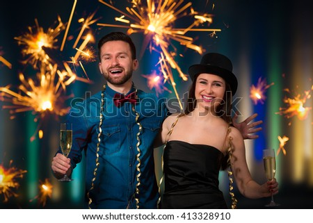 Young couple with champagne flutes celebrating New year's eve and having fun - stock photo