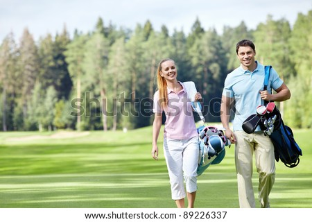 Young couple with clubs on the golf course - stock photo