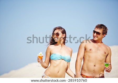 Young couple with cocktails having beach party - stock photo