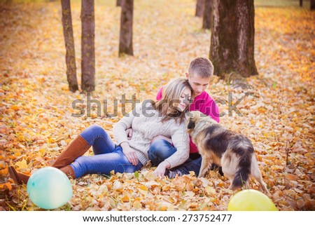 young couple with dog in autumn park