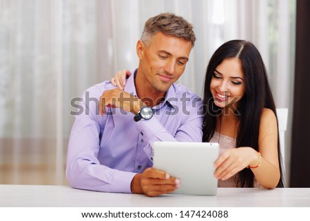 Young couple with electronic tablet at home