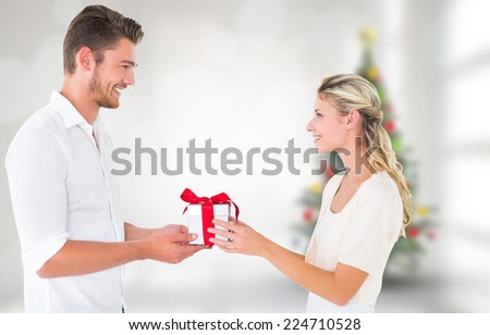 Young couple with gift against blurry christmas tree in room - stock photo