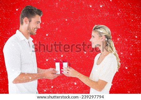 Young couple with gift against red background - stock photo
