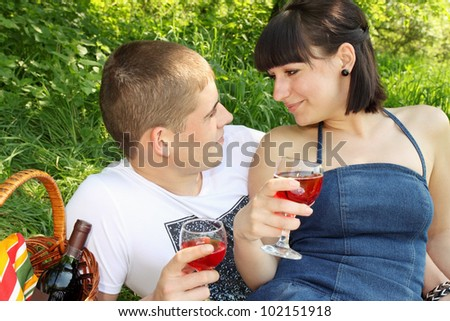 Young couple with glasses of wine looking at each other