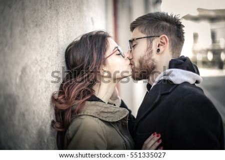 Young couple with glassses kissing on the street