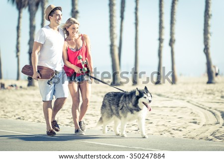 Young couple with husky dog in Santa monica. Concept with people and animals - stock photo