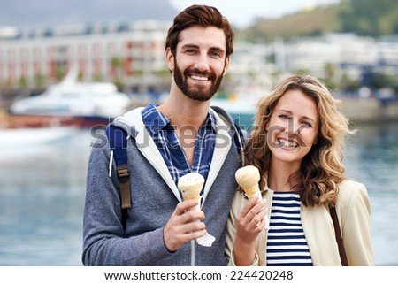 young couple with icecream portrait smiling and having fun - stock photo