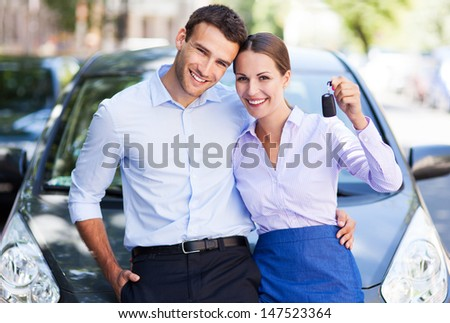 Young couple with keys to new car - stock photo