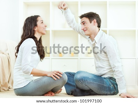 Young couple with keys to new home - stock photo