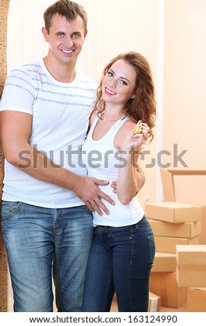 Young couple with keys to your new home on room background  - stock photo