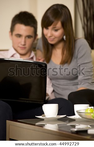 Young couple with laptop and coffee. Focus on coffee cup - stock photo