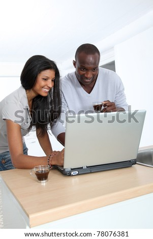 Young couple with laptop computer in home kitchen - stock photo