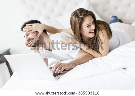 Young couple with laptop in the bed - stock photo