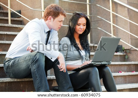 Young couple with laptop on the steps. - stock photo